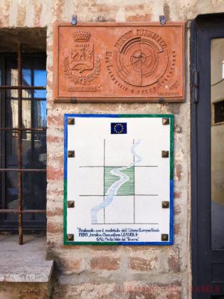 Targa per celebrare i lavori di ripavimentazione fatti grazie al comune di Marsciano e il GAL media valle del Tevere. Sulla targa è disegnato un fiume che passa dentro un quadrato verde, con in alto la bandiera dell'Unione Europea.