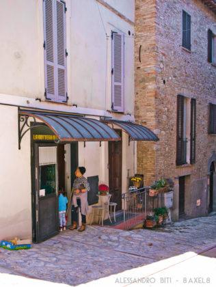 """Ingresso del negozio di alimentari """"La bottega di Casa Breccia"""", riaperto dopo tanti anni, con una cliente con un bambino che stanno per entrare."""