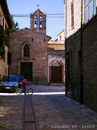 Un bambino in bicicletta percorre la via principale, con infondo la chiesa e una stella cometa di luci di Natale.