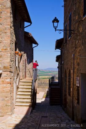 Vicolo con alcune scale per entrare nelle case, con una persona che sta fotografando la campagna umbra.